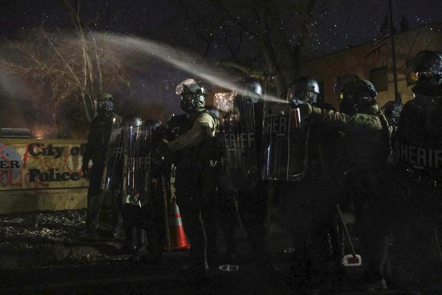 A police officer releases a chemical irritant at a protester on the other side of the fence of the Brooklyn Center Police Department, in Brooklyn Center, Minnesota, April 13, 2021. (Photo by Leah Millis/Reuters)