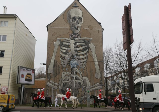 Carnival revellers ride horses past a large mural on the side of a house during the traditional Rose Monday carnival parade in Cologne February 16, 2015. (Photo by Wolfgang Rattay/Reuters)