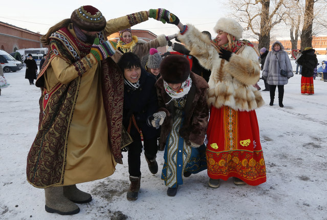 People dressed in traditional Russian clothes dance during the celebration of Orthodox Christmas in St.Petersburg, Russia, Thursday, January 7, 2016. (Photo by Dmitry Lovetsky/AP Photo)