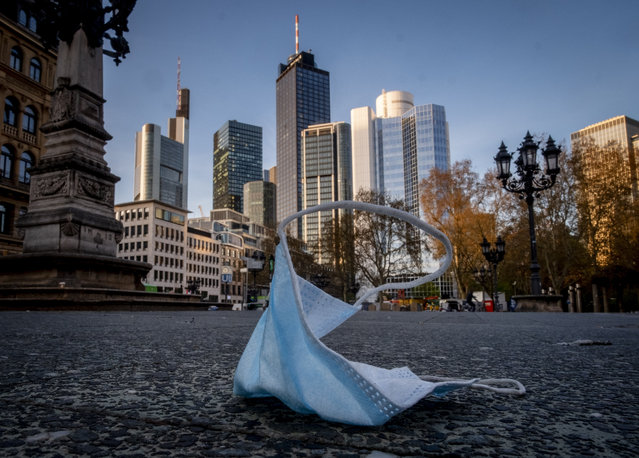 A face mask is left back on the opera square in Frankfurt, Germany, Saturday, April 24, 2021. From the weekend on a curfew becomes effective to avoid the outspread of the coronavirus. (Photo by Michael Probst/AP Photo)