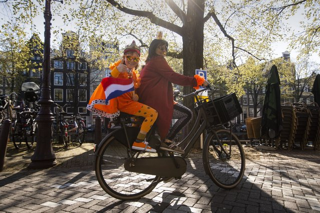 A mother and her daughter, flashing a thumbs up and wearing an orange King's robe and the Dutch flag, ride along Prinsengracht canal on King's Day in the center of Amsterdam, Netherlands, Tuesday, April 27, 2021. The Dutch were celebrating their king's birthday Tuesday in muted fashion as a coronavirus lockdown prevented large-scale street parties for the second year running. (Photo by Peter Dejong/AP Photo)