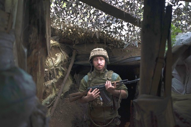 A Ukrainian poses for a photo at a fighting position on the line of separation from pro-Russian rebels near Toretsk, eastern Ukraine, Thursday, May 6, 2021. (Photo by Felipe Dana/AP Photo)