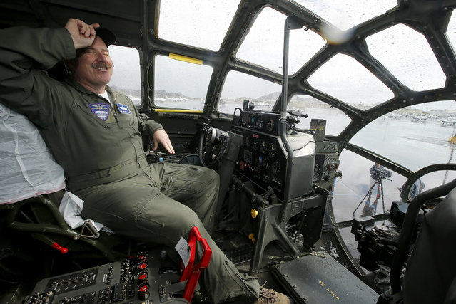 """Col. Mark Novak, of the Commemorative Air Force, pauses as he sits in the cockpit of the CAF's World War II era B-29 Superfortress bomber plane """"FIFI"""" after it landed at Deer Valley Airport, Monday, February 23, 2015, in Phoenix. The B-29 is on a tour of Arizona and California. (Photo by Ross D. Franklin/AP Photo)"""