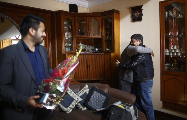 Deepak Malhotra (R), who along with his son Dikesh Malhotra (L) were travelling on a Turkish Airlines plane that overshot the runway at Tribhuvan International Airport, is greeted by a family member at their home in Kathmandu March 4, 2015. According to local media, all passengers and crew members were rescued. REUTERS/Navesh Chitrakar