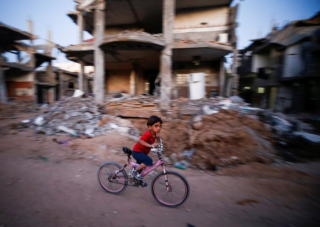 A boy rides his bicycle near the rubble of a house which was destroyed by Israeli air strikes during the Israel-Hamas fighting, in Gaza Strip, May 23, 2021. (Photo by Ahmed Jadallah/Reuters)