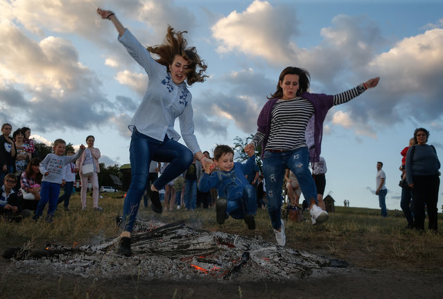 Ukrainians jump over a fire in Kiev, Ukraine, 06 July 2017, as they celebrate the traditional pagan holiday of Ivana Kupala. Ivana Kupala is celebrated, during the summer solstice, on the shortest night of the year, marking the beginning of summer and is celebrated in Ukraine, Belarus, Poland and Russia on the night of 06 July. People sing and dance around bonfires, play games and perform traditional rituals. Young people jump over bonfires in order to test their bravery. Couples holding hands jump over the flames to test their love. If the couple does not succeed it is predicted to split up. Traditionally, children and young unmarried women wear wreaths of wild flowers on their heads to symbolize purity. (Photo by Sergey Dolzhenko/EPA)