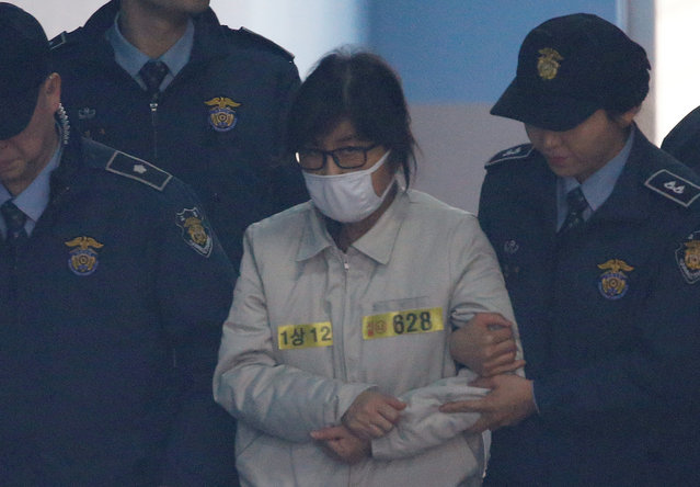 Choi Soon-sil (wearing white mask), a long-time friend of South Korean President Park Geun-hye who is at the center of the South Korean political scandal involving Park, arrives for her first court hearing  in Seoul, South Korea, December 19, 2016. (Photo by Kim Hong-Ji/Reuters)