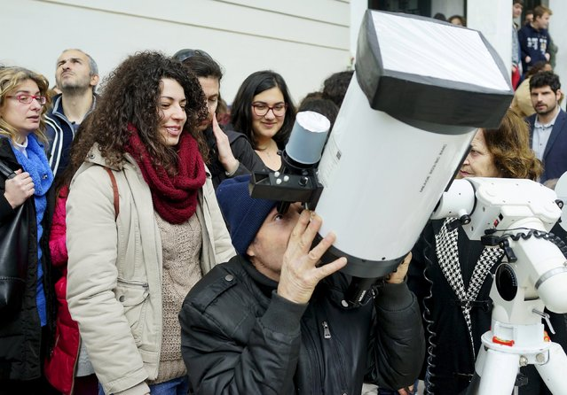 Amateur astronomers and students use a telescope to watch a partial eclipse of the sun in Athens March 20, 2015. (Photo by Yannis Behrakis/Reuters)