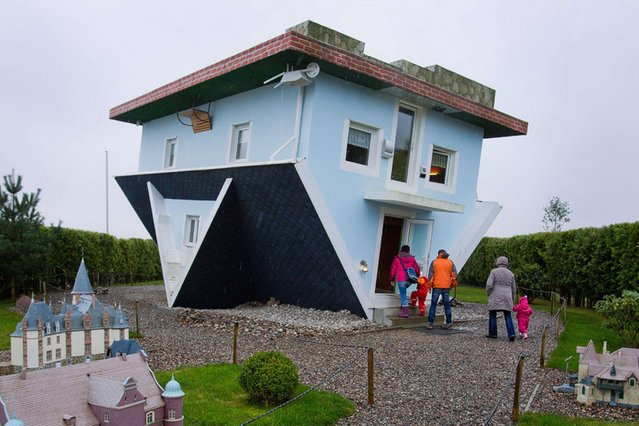 Visitors enter a house standing upside down in Trassenheide on the Baltic Sea island of Usedom, northeastern Germany, on November 5, 2013. The house was constructed in 2008 and the house interior is designed upside down as well. (Photo by Jens Buettner/AFP Photo)