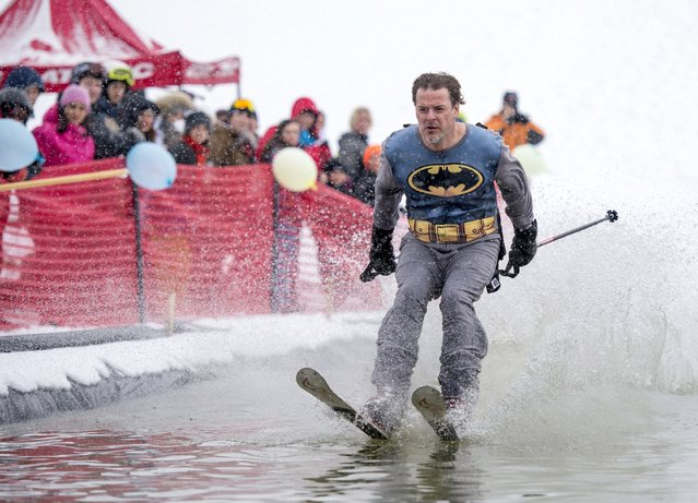 A competitor dressed as Batman skims across the water during the Pond Water Skipping event at Mont Cascades in Cantley, Quebec, Saturday, March 21, 2015. (Photo by Justin Tang/AP Photo/The Canadian Press)