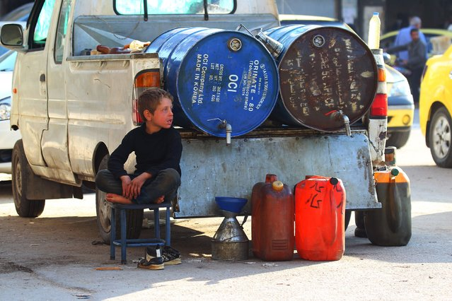A boy sits near containers of gasoline and kerosene for sale in the rebel-controlled city of Idlib, Syria November 7, 2015. (Photo by Ammar Abdullah/Reuters)