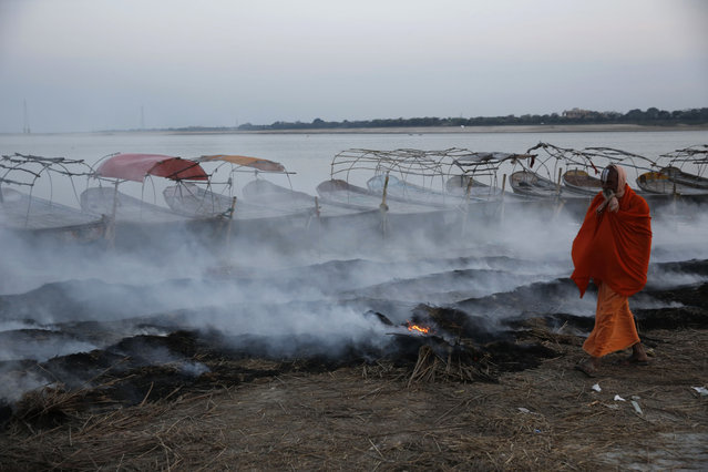 A sadhu, or Hindu holy man, walks past burning hay on the banks of the Sangam, the confluence of the rivers Ganges, Yamuna and the mythical Saraswathi, in Allahabad, India, Tuesday, March 17, 2015. Hay had been used to cover the slippery banks of the Sangam in order to prevent accidents with thousands gathering during the Magh Mela festival that ended in February. (Photo by Rajesh Kumar Singh/AP Photo)
