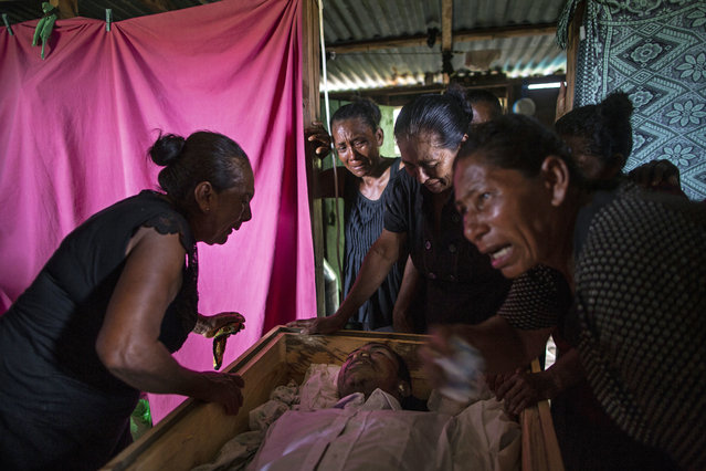 In this September 2, 2018 photo, Sonia Wills, left, accompanied by relatives, mourns over the coffin that contains the remains of her 31-year-old son Miskito diver Oscar Salomon Charly, during a wake in her home in Cabo Gracias a Dios, Nicaragua. Thousands of men across the Mosquitia region of Honduras and Nicaragua depend on lobster fishing to ease poverty, and hundreds have been stricken with the bends. Some end up paralyzed. Some killed. (Photo by Rodrigo Abd/AP Photo)