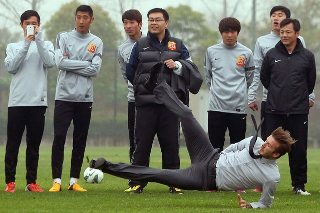 Football superstar David Beckham (R) falls down after illustrating how to take a free kick during a visit to the Zall Football Club in Wuhan, central China's Wuhan province on March 23, 2013. (Photo by AFP Photo)