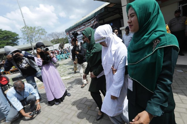 An Acehnese woman (2-R) escorted by sharia police before being canned as punishment for having a sexual relationship outside of marriage in Banda Aceh, Aceh, Indonesia, 31 January 2019. Aceh is the only province in Indonesia that has implemented Sharia law, which considers lesbian, gay and bisexual relationships along with s*x outside of marriage as a punishable offence. (Photo by Hotli Simanjuntak/EPA/EFE)