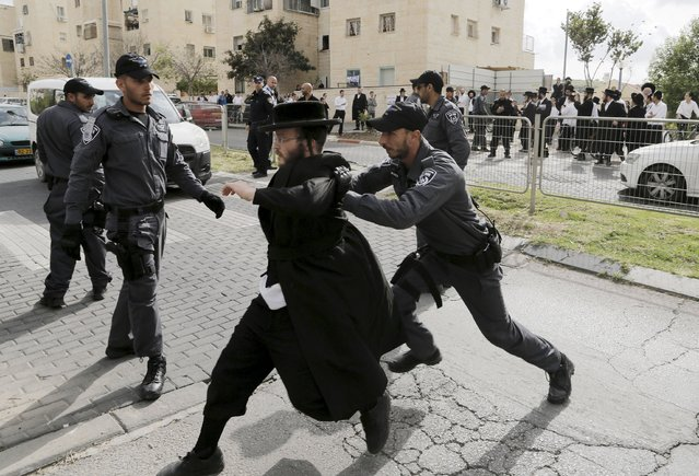 An Israeli policeman pushes an ultra-Orthodox Jewish protester after he tried to block a street in the town of Beit Shemesh, near Jerusalem April 16, 2015. Dozens of ultra-Orthodox Jewish protesters on Thursday demonstrated against construction at a site they believe contains ancient Jewish graves. (Photo by Ammar Awad/Reuters)