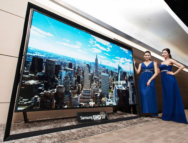 In this undated handout photo released by Samsung Electronics Co. Monday, December 30, 2103, models pose with a Samsung Electronics' 110-inch UHD TV. Samsung on Monday said a 110-inch UHD TV that has four times the resolution of standard high-definition TVs is going on sales for about $150,000 in South Korea. (Photo by AP Photo/Samsung Electronics Co.)