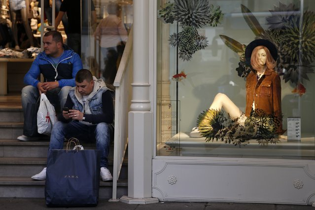 Men with Zara and H&M shopping bags sit at the entrance of Stradivarius, a clothing store owned by Spanish global group Inditex in central Madrid March 13, 2015. The families behind Zara-owner Inditex and H&M will need to fend off fast-moving competitors if they are to replicate online the winning formulae that made them the world's top two fashion retailers. (Photo by Susana Vera/Reuters)