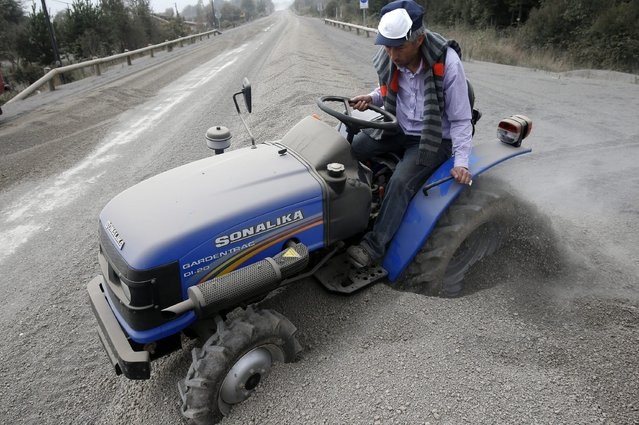 A man tries to remove ash from a small tractor at the Ensenada locality, outskirts of Calbuco volcano, which erupted this 22 April after 40 years without activity, Los Lagos region, south of Chile, on 23 April 2015. More than 4,000 people have been evacuated so far because of the two recorded eruptions of the volcano, officials said. (Photo by Felipe Trueba/EPA)