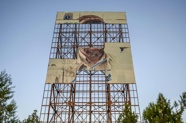 A billboard with a shattered picture of late Afghan commander Ahmed Shah Massoud is seen in Kabul on September 14, 2021. (Photo by Bulent Kilic/AFP Photo)
