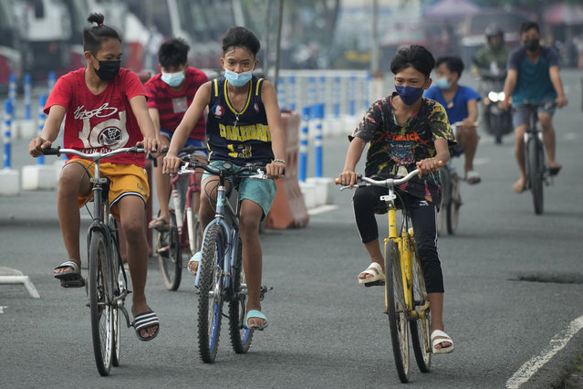 Boys wearing face masks to prevent the spread of the coronavirus ride their bikes outside Manila's COVID-19 Field Hospital, Philippines on Thursday, September 2, 2021. (Photo by Aaron Favila/AP Photo)
