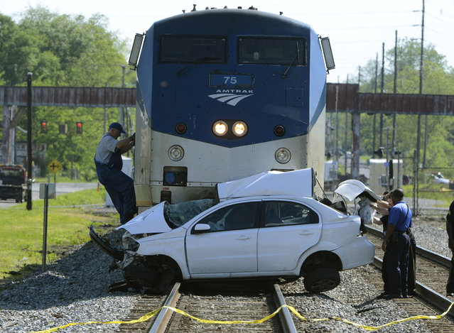 A conductor climbs to the cab of a locomotive after a collision between an Amtrak train and a car in Bessemer, Ala., Wednesday, April 22, 2015. The driver of the car drove around the crossing guards, according to Deputy Chief Mike Roper of the Bessemer Police Department. (Photo by Mark Almond/AL.com via AP)