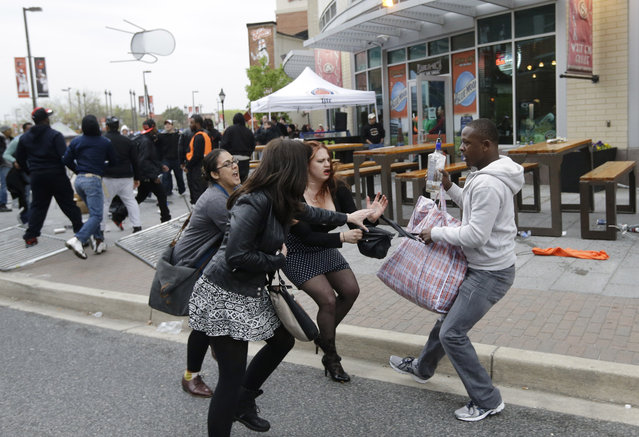 A protestor, right, pulls a bag away from a group of women after a rally for Freddie Gray, Saturday, April 25, 2015, in Baltimore. (Photo by Patrick Semansky/AP Photo)