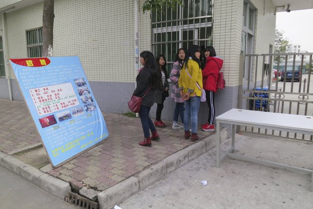 A group of young female migrant workers look for work outside a factory in the Pearl River Delta industrial hub of Dongguan, China February 25, 2016. The workers were employed on temporary contracts before the Chinese New Year holiday, and had no work to return to after the holiday, forcing them to look for new jobs. Millions of migrant workers streaming back to China's industrial heartland after the long lunar New Year break are facing an uncertain future, as smaller factories in particular struggle to cope with anemic orders and rising inventories. (Photo by James Pomfret/Reuters)