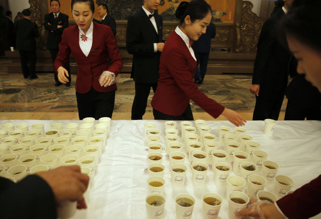 Attendants arrange tea cups ahead of the second plenary session of the National People's Congress (NPC) in Beijing, China, March 9, 2016. (Photo by Damir Sagolj/Reuters)