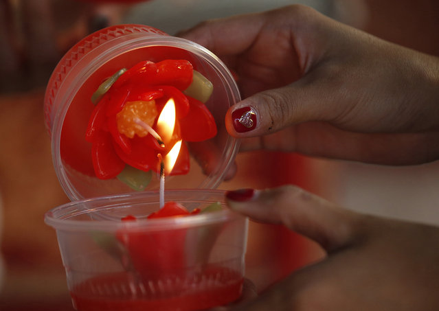 In this Wednesday, January 30, 2019, photo, ethnic Chinese-Thai light candles after praying at the Leng Nuei Yee Chinese temple for the upcoming Lunar New Year in Bangkok, Thailand. (Photo by Sakchai Lalit/AP Photo)
