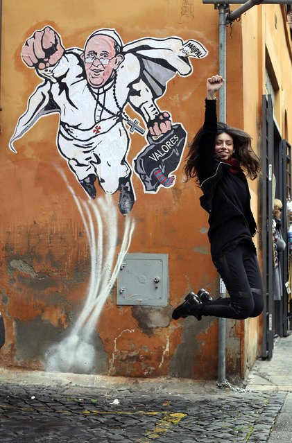 A woman jumps as a friend (not seen) takes a photo in front of a large drawing of Pope Francis depicting him as a superhero near the Vatican January 29, 2014. The Argentinian Pope is shown taking off into air with his right fist clenched in a classic Superman style. (Photo by Alessandro Bianchi/Reuters)