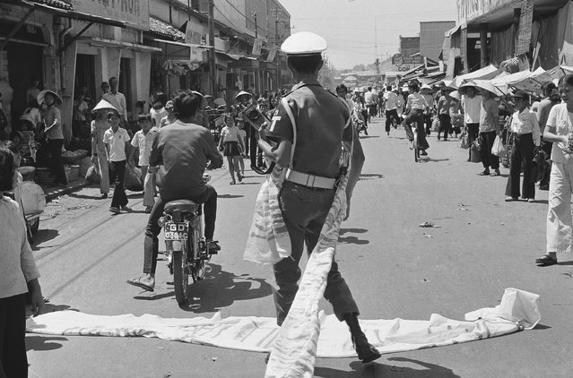 A Saigon student demonstrator hastily flees after a policeman grabbed his antigovernment banner, Thursday, April 9, 1975. About 30 students protested the draft and demanded the ouster of South Vietnamese President Nguyen Van Thieu. (Photo by Dang Van Phuoc/AP Photo)