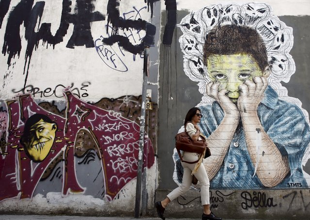 A pedestrian walks past a graffiti in central Athens, April 26, 2015. (Photo by Kostas Tsironis/Reuters)