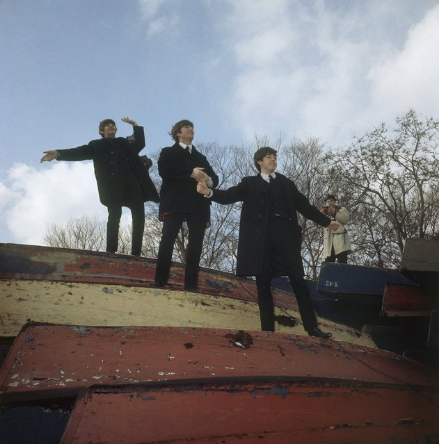 In this February 10, 1964, file photo, three members of the Beatles pose on a stack of rowboats in New York's Central Park. From the top are: Ringo Starr, John Lennon and Paul McCartney. (Photo by AP Photo)