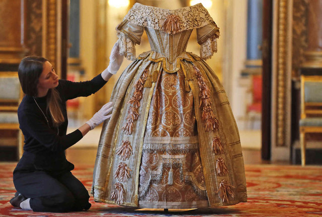 A member of the Palace staff arranges Queen Victoria's Stuart Ball costume which is part of an exhibition to mark the 200th anniversary of the birth of Queen Victoria (1819–1901) this year at Buckingham Palace in London, Tuesday, April 2, 2019. The exhibition, Queen Victoria's Palace at the Summer Opening of Buckingham Palace from 20 July – 29 September 2019, will tell the story of her 62-year reign and her life at Buckingham Palace, which began when she ascended to the throne in June 1837. (Photo by Frank Augstein/AP Photo)