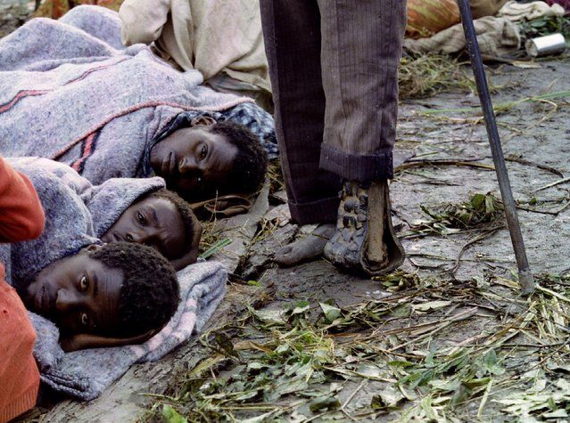 An amputee moves past three Tutsi refugees huddled together to protect themselves against the cold and damp in a camp in southern Rwanda, May 20, 1994. (Photo by Corinne Dufka/Reuters)