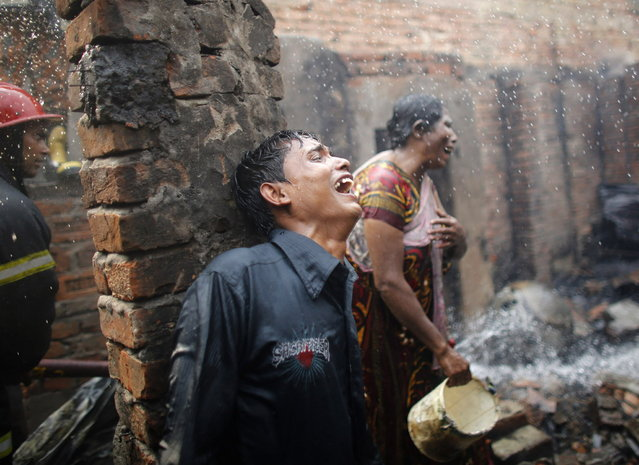 People cry after losing all of their belongings in a fire at a slum at Mirpur in Dhaka February 11, 2014. According to local media, at least 200 shanties and 20 shops were destroyed in the fire on Tuesday, which was caused by an electric short circuit at a slum in the Mirpur area of Dhaka. (Photo by Andrew Biraj/Reuters)