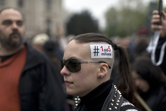 """A woman wears a sticker reading """"One in Five Million"""" in Serbian Latin letters, the slogan of protests against populist Serbian president Aleksandar Vucic, in Belgrade, Serbia, Saturday, April 13, 2019. Thousands of people protested against Serbia's populist President Aleksandar Vucic on Saturday as riot police deployed inside the country's parliament, saying they wanted to prevent the opposition from storming the building. (Photo by Marko Drobnjakovic/AP Photo)"""