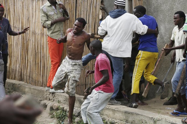 Jean Claude Niyonzima, a suspected member of the ruling party's Imbonerakure youth militia, flees from his house while surrounded  by a mob of demonstrators protesting against President Pierre Nkurunziza's decision to seek a third term in office, in the Cibitoke district of Bujumbura, Burundi, Thursday May 7, 2015. (Photo by Jerome Delay/AP Photo)