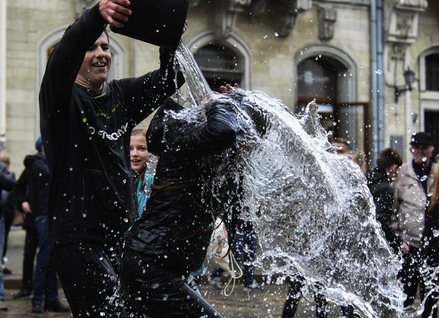 Ukrainians pour water on each other on a street in downtown of the West-Ukrainian city of Lviv, Ukraine, 29 April 2019. The custom of pouring water is an ancient spring cleansing rite that takes place on the Easter Monday. (Photo by Markiian Lyseiko/EPA/EFE)