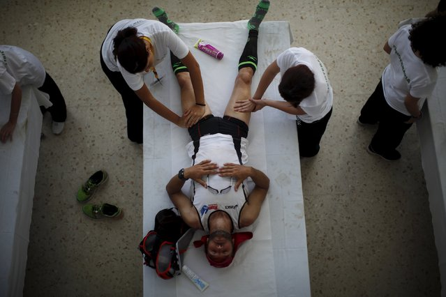 A runner is treated by physiotherapists as he takes a break during the XVIII 101km international competition in Setenil de las Bodegas, southern Spain, May 9, 2015. (Photo by Jon Nazca/Reuters)
