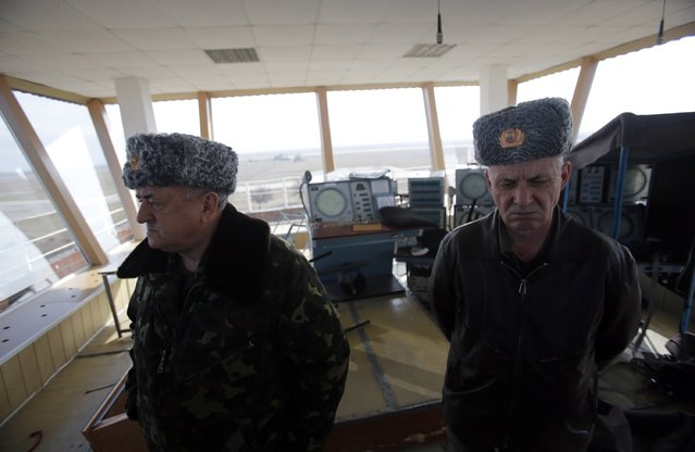 Ukrainian Army General and Hero of Ukraine Yuri Tishkov, left, surveys broken equipment at the air control tower for Kirov military airfield, in Feodosia, Crimea, Ukraine, Saturday, March 1, 2014. General Tishkov accused armed men, who he said were Russian troops, of braking into the air control tower and smashing much of the equipment on Friday, and then left the area. (Photo by Darko Vojinovic/AP Photo)