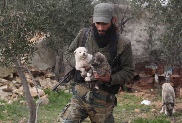 """""""Free Syrian Army"""" fighter Ahmed al-Hussein carries puppies near the frontline against forces loyal to Syria's President Bashar al-Assad in Aziza village in the southern countryside of Aleppo, Syria, January 28, 2015. Hussein, 31, said he takes care of all the dogs living in the area. (Photo by Hosam Katan/Reuters)"""