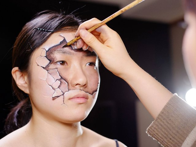 """Artist Hikaru Cho paints her model's face as part of Amnesty International's global campaign """"My Body My Rights"""" on sexual and reproductive rights. (Photo by Jim Marks/PA Wire)"""