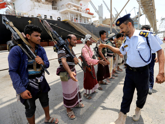 Yemeni coast guard officer shakes hands with members of the Houthi movement during withdrawal from Saleef port in Hodeidah province, Yemen on May 11, 2019. (Photo by Abduljabbar Zeyad/Reuters)
