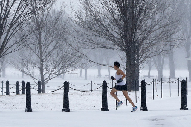 An unidentified man braves the elements as he runs on the National Mall as snow falls in Washington, Monday, March 3, 2014. The National Weather Service has issued a Winter Storm Warning for the greater Washington Metropolitan region, prompting area schools and the federal government to close for the wintry weather. (Photo by Charles Dharapak/AP Photo)