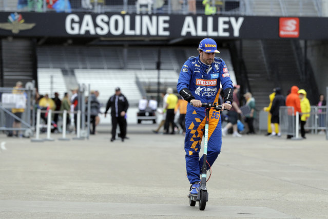 Fernando Alonso, of Spain, rides his scooter back to the garage after rain ended a practice session for the Indianapolis 500 IndyCar auto race at Indianapolis Motor Speedway, Sunday, May 19, 2019 in Indianapolis. (Photo by Darron Cummings/AP Photo)
