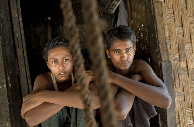 In this Monday, May 11, 2015, photo 16-year-old Sadik Hussein, left, and 17-year-old Noor Alam, hours after returning to their homes in Thetkabyin Village, north of Sittwe, western Rakhine state, Myanmar. They say they escaped from a human trafficking boat, where they sat for days with their knees bent into their chest, pressed up against other sweaty bodies in the cabin's rancid heat. (Photo by Gemunu Amarasinghe/AP Photo)