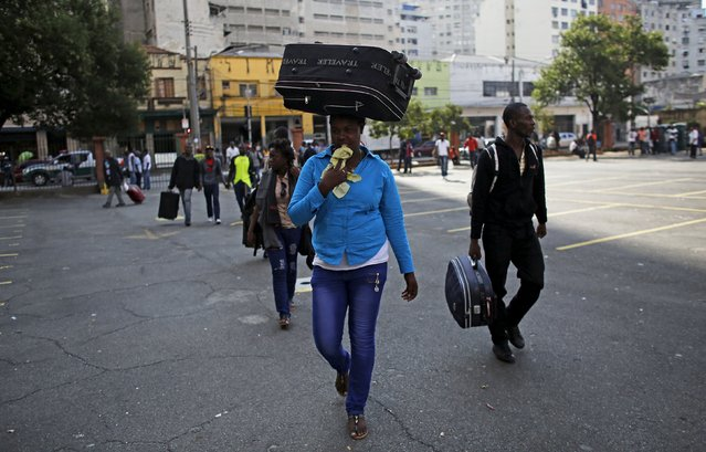 Haitian immigrants carry their luggage as they arrive at the Nossa Senhora da Paz Catholic Church, in the Glicerio neighborhood of Sao Paulo, Brazil May 20, 2015. Three years ago, the Brazil government announced the creation of a humanitarian visa that would be exclusively issued to Haitian refugees after the devastating 2010 earthquake on the island. (Photo by Nacho Doce/Reuters)