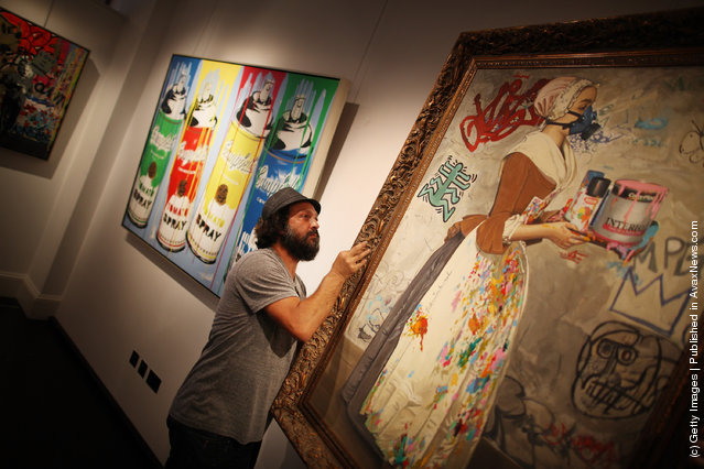 Artist Mr Brainwash helps to hang his painting  'Chocolate Vandal' at the Opera Gallery